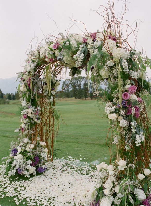 arbor canopy with curly willow branches, baby's breath, blush roses, lavender rosemary, and other greenery